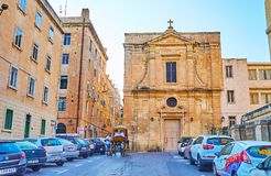 The facade of St Mary Magdalene church, Valletta, Malta. VALLETTA, MALTA - JUNE 19, 2018: The St Mary Magdalene church faces North street, occupied with parked royalty free stock images