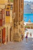 Steps in Valletta in Malta. VALLETTA, MALTA - JUNE 26, 2012:  Unidentified tourists exploring traditional buildings next to some steps in Valletta, in Malta Stock Images