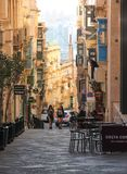 Two girls walk on straight street of Valletta between cafe chairs stock photos