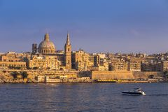Valletta, Malta - Motorboat and the famous St.Paul`s Cathedral w. Ith the ancient city of Valletta at sunset Stock Photography
