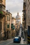 Basilica of Our Lady of Mount Carmel, Valletta, Malta. Valletta, Malta. Narrow street of Valletta in the morning with a view of Basilica of Our Lady of Mount Stock Images