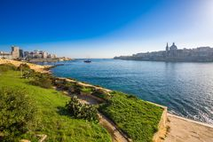 Valletta, Malta - a opinião da skyline da cidade antiga de Valletta e de Sliema no nascer do sol disparou da ilha de Manoel Fotos de Stock Royalty Free