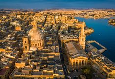 Valletta, Malta - Our Lady of Mount Carmel Church and St.Paul`s Cathedral from above at sunrise. With the ancient city of Valletta at background Stock Image