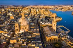 Valletta, Malta - Our Lady of Mount Carmel Church and St.Paul`s Cathedral from above at sunrise. With the ancient city of Valletta at background Royalty Free Stock Photography