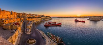 Valletta, Malta - Panoramic shot of an amazing summer sunrise at Valletta`s Grand Harbor with ships. And the ancient houses and walls of the maltese capital Royalty Free Stock Image