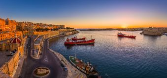 Valletta, Malta - Panoramic shot of an amazing summer sunrise at Valletta`s Grand Harbor with ships. And the ancient houses and walls of the maltese capital Stock Images