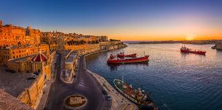 Valletta, Malta - Panoramic shot of an amazing summer sunrise at Valletta. `s Grand Harbor with ships and the ancient houses and walls of the maltese capital Royalty Free Stock Images