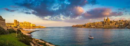 Valletta, Malta - Panoramic skyline view of the ancient city of Valletta and Sliema at sunrise. Shot from Manoel island at spring time with sailing boat, blue Royalty Free Stock Photography