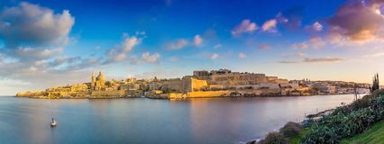 Valletta, Malta - Panoramic skyline view of the ancient city of Valletta and Sliema at sunrise shot from Manoel island at spring. Time with sailing boat, blue stock image