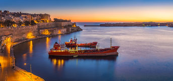 Valletta, Malta - Panoramic skyline view of Valletta and the Grand Harbor. On a beautiful summer morning minutes before sunrise with ships Stock Image