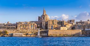 Valletta, Malta - Panoramic view of Saint Paul`s Cathedral and the ancient walls of Valletta. With sail boat in the morning Royalty Free Stock Photos