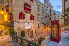 Valletta, Malta - Rode uitstekende Britse telefooncel en voetgangersbrug in Valletta stock fotografie