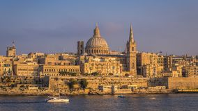 Valletta, Malta - Sailboat and the famous St.Paul`s Cathedral wi. Th the ancient city of Valletta at sunset Stock Photography