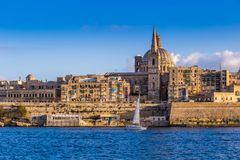 Valletta, Malta - Saint Paul`s Cathedral and the ancient walls of Valletta with sail boat Stock Photos