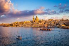 Valletta Malta - segla fartyg på väggarna av Valletta med domkyrkan för Saint Paul ` s och härlig himmel och moln Arkivfoto