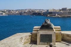 Valletta, Malta Siege War Memorial sculpture. Bronze soldier lying on a catafalque at the lower part of Saint Christopher Bastion,facing the Grand Harbour in Stock Photo