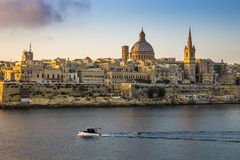 Valletta, Malta - St.Paul`s Cathedral and the ancient city of Va. Lletta with motorboat at sunrise Royalty Free Stock Photo