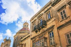 Valletta, Malta, Traditional buildings facade and church dome on blue sky background, under view. Valletta, Malta, Traditional buildings facade and church red Royalty Free Stock Image