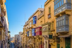 Valletta, Malta - Typical narrow street with colorful traditiona. L windows and balconies and clear blue sky on a summer day Royalty Free Stock Images