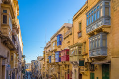 Valletta, Malta - Typical narrow street with colorful traditional windows. And balconies and clear blue sky on a summer day Stock Images