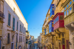 Valletta, Malta - Typical narrow street with colorful traditional windows. And balconies and clear blue sky on a summer day Stock Image