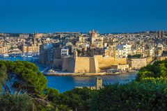 Valletta, Malta - The view from Valletta with trees, Island of S. Englea, Gardjola Gardens with watchtower, the Grand Harbour with boats and ships and clear blue Royalty Free Stock Photos