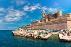 Valletta Skyline in sunny day, Malta. Valletta Skyline with fortress wall, boat pier and St. Paul`s Anglican Pro-Cathedral, Valletta, Capital city of Malta. View Royalty Free Stock Photos