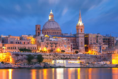 Valletta Skyline from Sliema at night, Malta. Valletta Skyline from Sliema with church of Our Lady of Mount Carmel and St. Paul`s Anglican Pro-Cathedral during Stock Photo