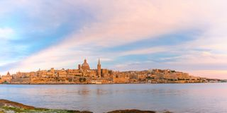 Valletta Skyline from Sliema at sunset, Malta. Panoramic view of Valletta Skyline at beautiful sunset from Sliema with churches of Our Lady of Mount Carmel and Stock Photos