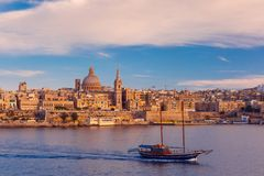 Valletta Skyline from Sliema at sunset, Malta. Valletta Skyline with ship at beautiful sunset from Sliema with churches of Our Lady of Mount Carmel and St. Paul` Royalty Free Stock Photo