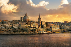 Valletta skyline waterfront at sunset. Malta. Panoramic view of Valletta at sunset with Carmelite Church dome and St. Pauls Anglican Cathedral. Malta Royalty Free Stock Photo