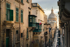 Valletta at sunrise, Malta. Narrow street of Valletta in the morning with a view of Basilica of Our Lady of Mount Carmel, Malta Stock Images