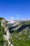 Valley. A rocky green valley an a deep blue sky in the background Stock Images