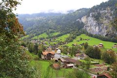 Valley in the Alps. A Swiss valley  is pictured here. The Alps tower over the valley and houses below. Green grass, and red roofed homes. Some clouds are rolling Royalty Free Stock Photo