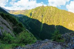 Valley of the balea stream in fagaras mountains. View from the rocky cliff on a steep slope. forested hillside in the distance. popular travel destination of royalty free stock photo