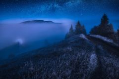 Valley covered with fog at night royalty free stock photography