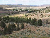 Valley down below. A view down hills into the farming valley and the small rural community of Gateway in Central Oregon on a sunny summer  day stock images