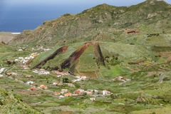 Valley of El Palmar in the Teno mountains with green slopes. In the center - volcanic hill like a sliced pie. Landmark of Tenerife royalty free stock photo