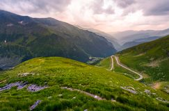 Valley in Fagaras mountains in afternoon. Beautiful nature scenery on a cloudy summer day. view from the grassy hillside with footpath. part of Transfagarasan stock photography