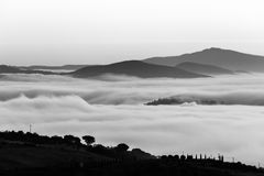 A valley filled by fog, with some hills and trees in the foregro. Und and other hills and mountains in the foreground Stock Photography