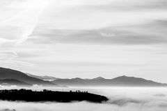 A valley filled by a sea of fog, with some hills resembling clif Stock Photography