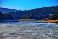 Valley with frozen lake and coniferous forest Royalty Free Stock Images