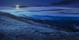 Valley on hillside of mountain range at night. Mountain panorama landscape. valley with stones in grass on top of the hillside of mountain range at night in full Stock Image