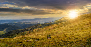 Valley on hillside of mountain range at sunset Royalty Free Stock Photos