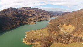 Valley with lake in the mountains. Turquoise water color of a lake among a mountain valley with snowy peaks in the background, aerial view stock footage