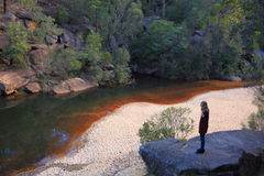 River bank valley landscape with woman. Young woman standing on a rock overlooking the riverbank landscape at Jellybean Pool, Blue Mountains. Traveling in Stock Photography