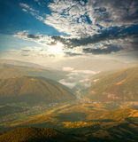 Valley in mountains at dawn, lighted by the sun, on sky Royalty Free Stock Images