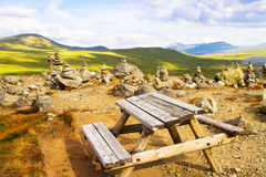 Valley in mountains and a place for rest with a table close to hiking route. Norway landscape. Royalty Free Stock Photography