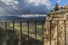 Valley with pastures and horticultural areas surrounded by mountains seen from a balcony with a metal railing in Ronda. Sunny day with a blue sky with white royalty free stock images