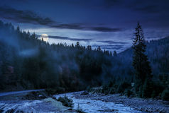 Valley with river in foggy forest at night. Valley with river in foggy forest. Spectacular autumnal landscape in mountains at night in full moon light Stock Photography